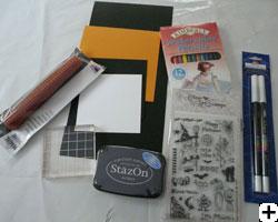 matériel pour projet scrapbooking avec étampe et crayon aquarelle